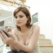 Young professional using a digital organizer while sitting in a modern stairwell. — Stock Photo