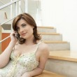 Young woman using a home phone while sitting on modern stairs. — Stock Photo