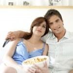 Пара смотреть телевизор вместе дома и едят попкорн — Стоковое фото