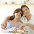 Couple watching tv together at home and eating popcorn. — Stock Photo