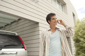 Businessman using a cell phone at home, standing by his car. — Stock Photo