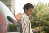 Businessman using a cell phone near modern building, leaning on his car. — Stock Photo