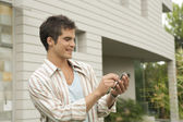 Businessman using a touch screen cell phone near a modern building. — Stock Photo