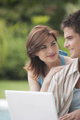 Couple looking at each other while using a laptop computer in home garden — Stock Photo