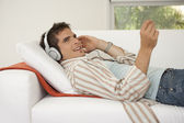 Side view of man laying down on a white sofa listening to music at home. — Stock Photo