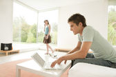 Young couple at home, using a laptop and making a phone call. — Stock Photo