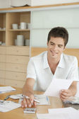 Hispanic man working on his home finances in the kitchen. — Stock Photo