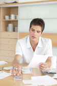 Young man working on his home finances in the kitchen. — Stock Photo