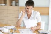 彼の家の台所で財政に取り組んでいる間彼の携帯電話を使用して男. — ストック写真