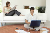 Couple at home using technology and reading the newspaper in living room. — Stock Photo