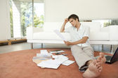 Young professional working on home finances in living room. — Stock Photo