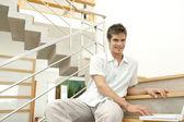 Genç profesyonel modern merdiven boşluğunda otururken bir dizüstü bilgisayar kullanarak. — Stok fotoğraf