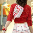 Back view of a young woman standing by a shop window, holding shopping bags. — Lizenzfreies Foto