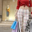 Part view of a young woman holding shopping bags in shopping street. — Stock Photo