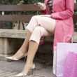 Sophisticated woman using a cell phone while sitting down with shopping bags. - Stock Photo