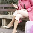 Fashionable young woman sitting down on a bench in a shopping street. — Stok fotoğraf