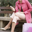 Young woman sitting down on a bench with her shopping bags — Stock Photo #21735887