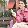 Foto Stock: Fashionable young woman sitting down on a bench in a shopping street.