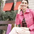 Fashionable young woman sitting down on a bench in a shopping street — Stock Photo
