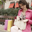 Young woman searching through her purse while sitting down with shopping bags. - Stock Photo