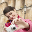 Foto Stock: Stylish young tourist taking pictures near a monument.