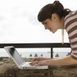 Young woman using a laptop outdoors — Stock Photo