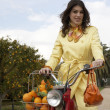Young fashionable woman standing with a motorbike and a shopping basket full of oranges — Stock Photo