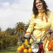 Young fashionable woman standing with a motorbike and a shopping basket full of oranges — Stock Photo #21736415