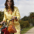 Woman standing with a motorbike and a shopping basket full of oranges — Stock Photo #21736427