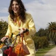 woman standing with a motorbike and a shopping basket full of oranges — Foto de Stock