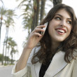 Stock Photo: Young attractive woman talking on a cell phone in a tree aligned street.