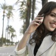 Young attractive woman talking on a cell phone in a tree aligned street. — Foto Stock