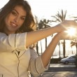 Portrait of a young woman holding the sun in her hands - Stock Photo