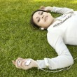 Young woman laying down on green grass — Stock Photo