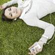 Young woman laying down on green grass — 图库照片