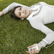 Young woman laying down on green grass — Стоковая фотография