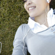 Stock Photo: Young woman listening to music on her headphones