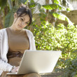Young professional woman using a laptop computer in the park on a sunny day. — Stock Photo