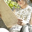 Young businesswoman reading a financial newspaper in a park — Stock Photo #21737555
