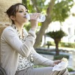Young businesswoman drinking water from a small plastic bottle while having a lunch break in the park. — Stock Photo