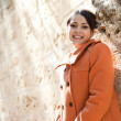 Young retro style woman wearing an orange coat and leaning on a sight's old stone walls — Stock Photo