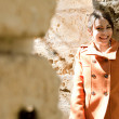 woman wearing an orange coat and leaning on a sight's old stone walls — Stock Photo