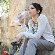 Young businesswoman sitting on a park steps drinking water from a plastic blue bottle. — Stock Photo