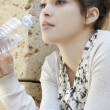 Portrait of a young businesswoman holding a bottle of mineral water. - Stock Photo
