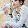 Stock Photo: Young woman driking water from a plastic blue bottle