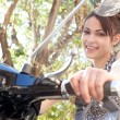 Young woman sitting on a classic motorbike — Stock Photo