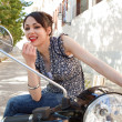 Attractive young woman using the mirrors on her motorbike to apply red lipstick — Stock Photo