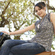 Young attractive woman sitting down on a motorbike with trees in the background — Stock Photo