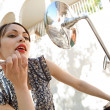 Stock Photo: Young womusing mirrors on her motorbike to apply red lipstick