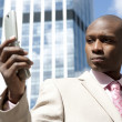 Close up of a businessman using a cell phone in the financial district. — Stock Photo #21738437